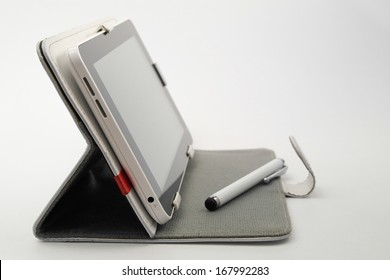 A white tablet on a tablet cover cum stand with capacitive pen on isolated background