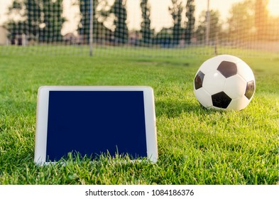 White tablet on grass field next to soccer ball, copy space, sports app concept