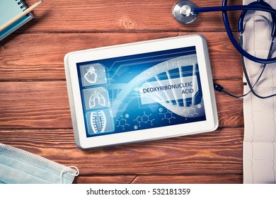 White tablet pc and doctor tools on wooden table