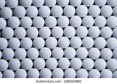 Tablettes blanches pliées sur un motif de production d'usine pharmaceutique en gros plan