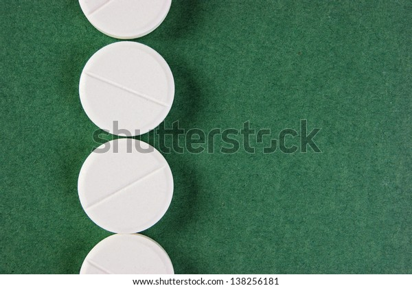 white tablets on a green background
