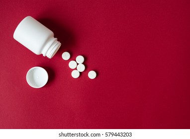 white tablets in plastic container top view