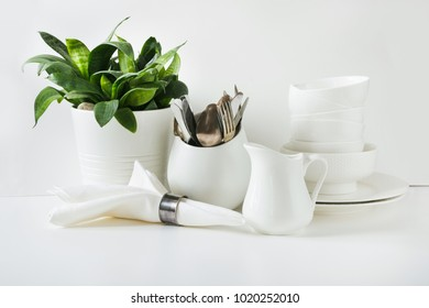 White tableware for serving. Crockery,dish, utensils and other different white stuff on white table-top. Kitchen still life as background. Copy space.