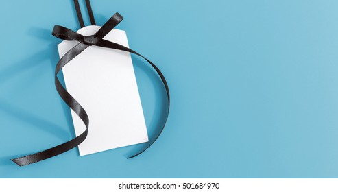 White tag with black ribbon on blue background