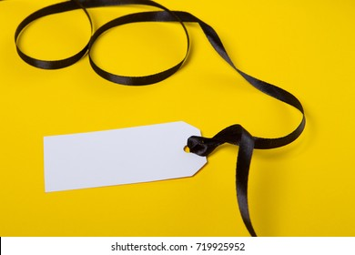 White tag with black ribbon on yellow background