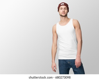 White tank top on a young man in jeans and hat, isolated with copy space, mockup.