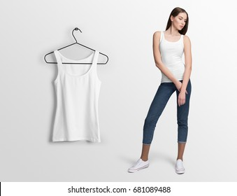 White tank top, sleeveless t-shirt on a young woman in jeans, isolated, mockup. Hanging tank top, against empty wall.
