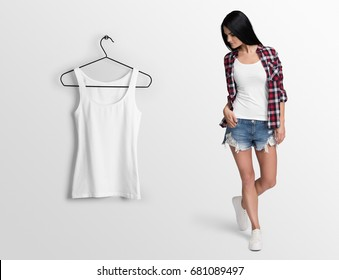 White tank top, sleeveless t-shirt on a young woman in shorts and checked shirt, isolated, mockup. Hanging tank top, against empty wall.
