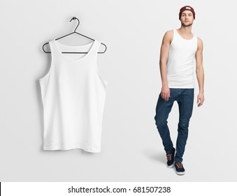 White tank top, sleeveless t-shirt on a man in jeans and hat, isolated, mockup. Hanging tank top, against empty wall.