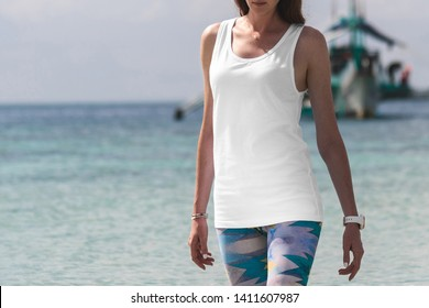 White tank top t-shirt on a young woman in leggins, front view mockup, on a beautiful beach