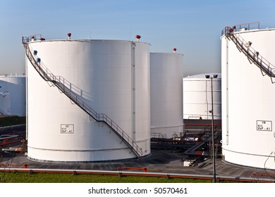 white tanks in tank farm with blue clear sky