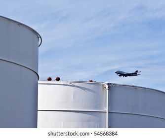 white tanks in tank farm with blue clear sky and aircraft in approach