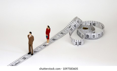 White tape measure with miniature people. The gender gap concept in employment and promotion.