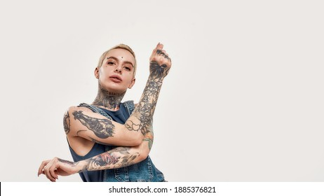 A white tattooed woman with piercing dancing alone wearing a denim overall looking into a camera with her hands crossed in a motion on a white colored background