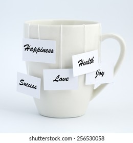 White tea cup with tea bags hanging out with different wishes - LOVE, JOY, SUCCESS, HEALTH, HAPPINESS.