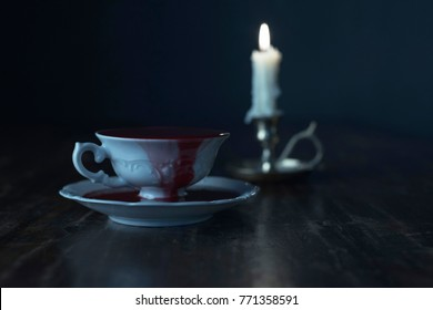 White tea cup in dark blood on dark wooden table with burning candle in candleholder.