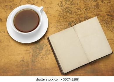 White Tea Cup And Vintage Notebook With Blank Brown Page And Gold Pen On The Old World Map Background. Overhead View. Travel Or Adventure Concept With Arrangement On The Old Map.