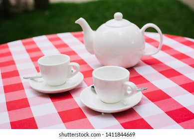 White tea service for two. Tea pair with a teapot and a milk jug on a bright red checkered tablecloth