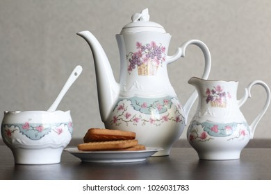 white tea set with biscuits and Apple