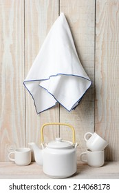 A white tea set on a rustic whitewashed setting with a towel hanging on the wall.