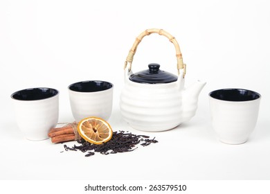 White tea set of three cups and teapot on a white background with tea, cinnamon and lemon