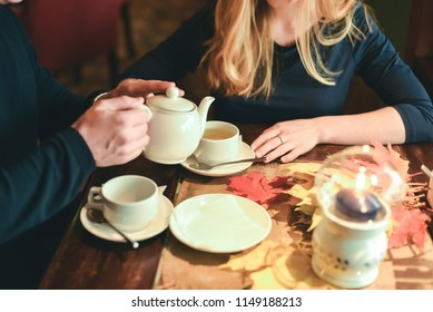 white teapot cup tea autumn leaves hands