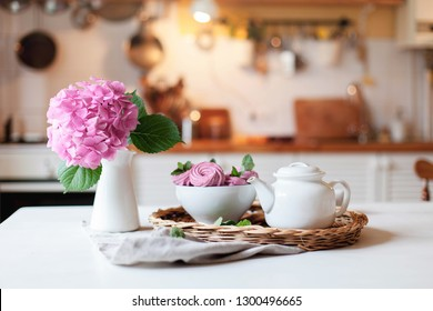 White teapot, pink cupcakes and hydrangea flowers on kitchen table. Breakfast with sweets is serving on straw tray. Tea time, cozy home atmosphere hygge. Still life for Women`s Day.