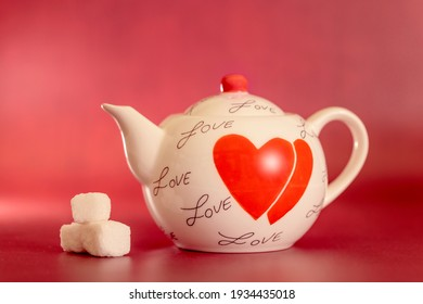 A white teapot with a red handle on the lid, black words 'love' and two red lovehearts on shown with three sugar lumps, shot against a red background with space for text, soft focus image, shallow dof