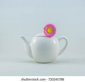 A White Teapot with a yellow and pink flower.