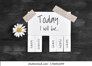 White tear-off stub note with text 'Today I will be...' and words 'happy, beautiful, brave, helpful' and 'strong' on dark black background with daisy flower