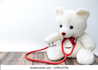 The white Teddy bear doctor with the red EMT sitting on the wooden floor.