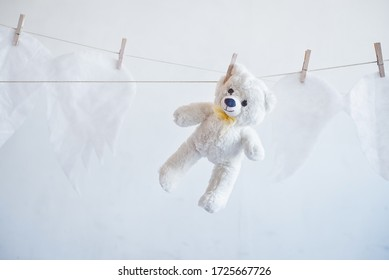 white teddy bear hanging on a clothesline