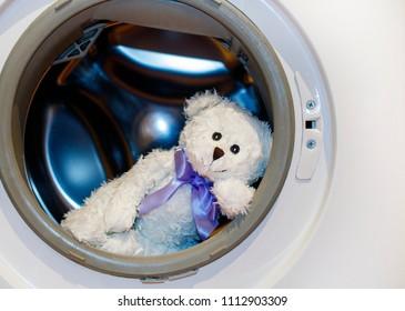 White teddy bear lies in the washing machine