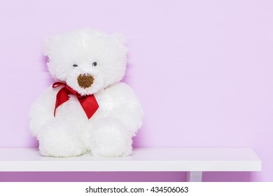 White teddy bear on shelf. White doll bear on the pink background.