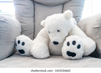White teddy bear toy slouching on a plush grey nursery chair. Backlit with natural sunlight.