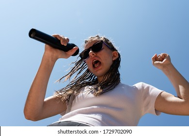 White teenager with hair braids wearing a white top and sun glasses singing a song with a black microphone at the right hand and the sky and the sunlight at the background. Horizontal photo