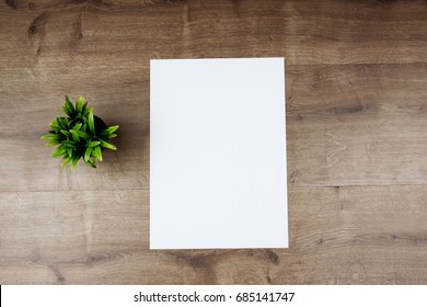 White template paper and flower on wooden background