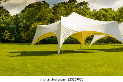 A white tent or marquee in a green field.