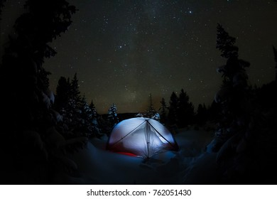 White tent under the starry sky and the milky way in the trees in the winter mountains at night.