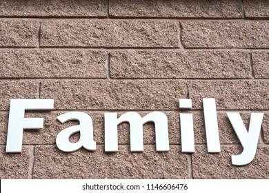 "White text ""Family"" wrote on the brown brick wall."