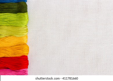 White textile canvas with colorful threads and a blank space as a background.