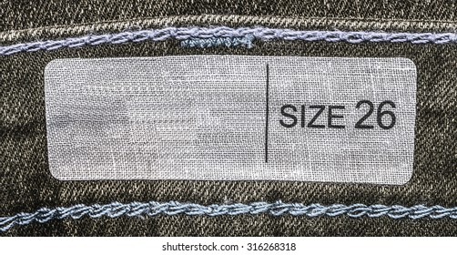 white textile label on brown denim background, size