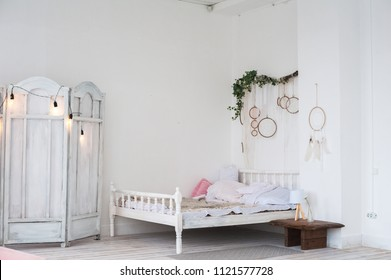 White textured bedroom in the style of shabby. Bed in an ecological style and Loft style. Rustic dream catchers on a white wall. screen diy