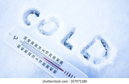 White thermometer with cold sign written in the snow in cool colors