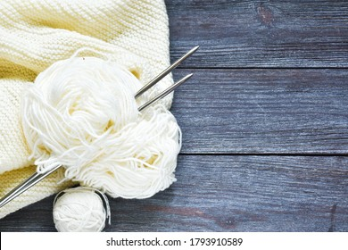 White threads and knitting needles and a knitted scarf on a wooden background. Copy space. Top view.Knitting concept.