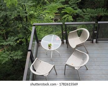 自然な眺めのバルコニーに座る白い椅子と3つ。