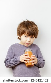 White three years boy drinking pumpkin smoothie from the jar using metal straw