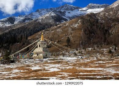 White Tibetan Prayer Stupa, Tibetan Prayer Flags - Picturesque winter scenery - Four Girls Mountain National Park in Sichuan Province, China. Shuangqiao Valley, Snow Capped Mountains. Siguniangshan