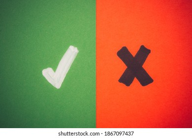 White tick symbol and black cross sign on color green red paper background. Correct or false, accept or rejected, yes or no, right or wrong, ok or not ok evaluation quiz concept.