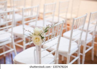 White tiffany chairs set up for ceremony with white rose posts on the end chair on aisle